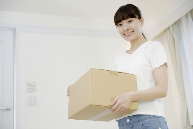 ダンボールの箱を持つ女性