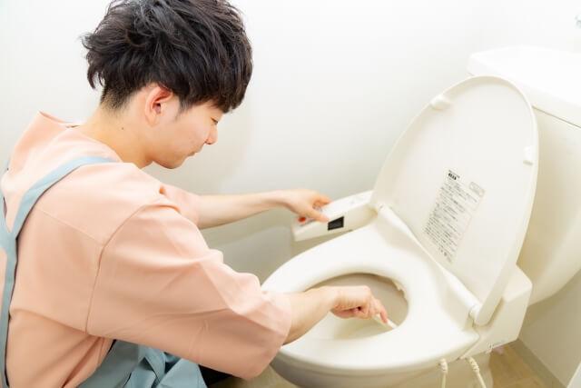 トイレ掃除をする男性
