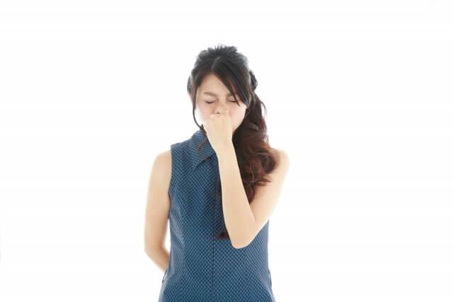 強烈な臭いに鼻をつまむ女性