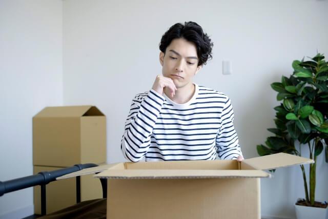 引っ越し作業中に悩む男性